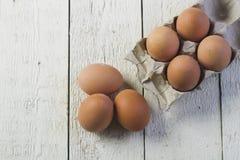Eier in einem Pappbehälter auf weiße Bretter Stockfotos