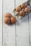Eier in einem Pappbehälter auf weiße Bretter Stockbild