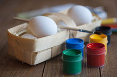 Eier in einem Weidenkorb, Farbe mit einer Bürste Lizenzfreie Stockbilder
