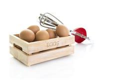 Eier in einer Holzkiste mit altem rotem Schneebesen Stockfotografie