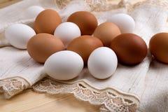 Eier eingewickelt im Stoff auf hölzerner Tabelle Stockfotografie