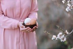 Eier für Ostern mit einem Zweig von Frühlingsblumen in den Händen eines Mädchens lizenzfreie stockfotos
