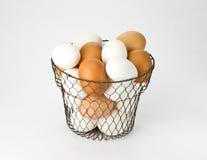 Eier im Drahtweinlese-Eikorb Stockfotografie