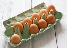 Eier im Eikasten auf weißem hölzernem Hintergrund Stockbilder