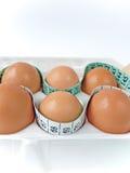 Eier im Karton mit messendem Band 2 Lizenzfreie Stockfotos