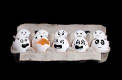 Eier im Kasten mit unterbrochenem Ei auf schwarzem Hintergrund Lizenzfreies Stockbild