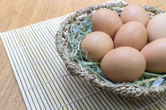 Eier im Korb auf hölzernem Stockfotos