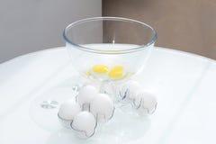 Eier im Oberteil nahe der Schüssel mit einem defekten Ei Lizenzfreie Stockbilder