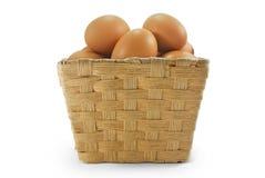 Eier im Rattankorb Stockbilder