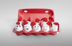 Eier kleideten in den Weihnachtsmann-rot-weißen Hüten an Lizenzfreie Stockfotos
