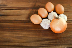 Eier, Knoblauch, Zwiebel auf einem braunen Holztisch Lizenzfreie Stockbilder