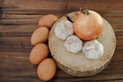 Eier, Knoblauch, Zwiebel auf einem braunen Holztisch Stockfoto
