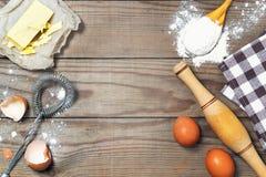Eier, Mehl, Butter auf dem Holztisch Grundlegender Backenhintergrund Lizenzfreie Stockfotos