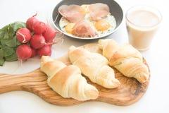 Eier mit Prosciutto und frischen gebackenen Hörnchen Stockfoto