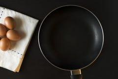 Eier mit Serviette auf schwarzem Hintergrund Stockbild