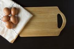 Eier mit Serviette auf schwarzem Hintergrund Stockfotos