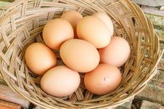 Eier und hölzerner Korbhintergrund des Esters Lizenzfreie Stockfotos