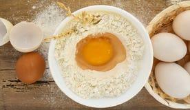 Eier und Mehl auf Holztisch lizenzfreie stockfotografie