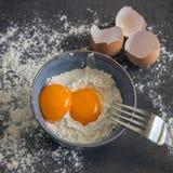 Eier und Mehl in der blauen Schüssel Bestandteile für Hauptbacken De Stockfoto