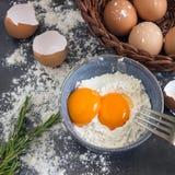 Eier und Mehl in der blauen Schüssel Bestandteile für Hauptbacken De Lizenzfreies Stockfoto