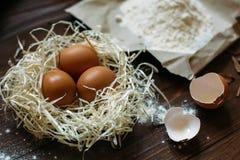 Eier und Mehl sind auf der dunklen Tabelle Stockbilder