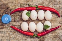 Eier und rote Pfeffer in Form eines Munds mit den Zähnen Blätter sind zu den Zähnen und zur Zahnseide fest Säubern Ihr stockfotos