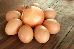 Eier und Zwiebel auf einem braunen Holztisch Stockfotos