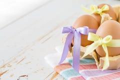 Eier verziert mit Band auf weißem hölzernem Hintergrund Stockfoto