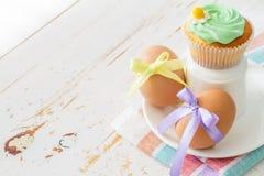 Eier verziert mit Band und kleinen Kuchen auf weißem hölzernem Hintergrund Stockfotografie