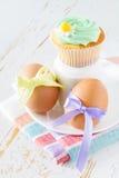 Eier verziert mit Band und kleinen Kuchen auf weißem hölzernem Hintergrund Lizenzfreies Stockfoto