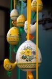 Eier, Wiesenschaumkraut und gestreifter Stoff Hübsche farbige Ostereier, die an den rbbons hängen Stockfotografie