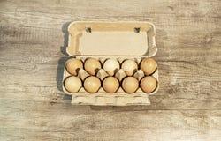 Eier, zehn braune Eier in einem Kartonpaket auf einem Holztisch Stockfotografie