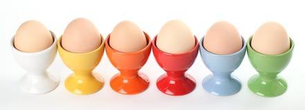 Eierdopjes met eieren Stock Afbeeldingen