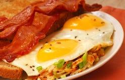 Eieren, bacon, toost en gebakken aardappelen Stock Afbeeldingen