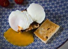 Eieren Benedict met vleeslapje vlees, tomaten en toost die op een blauwe plaat liggen stock foto's