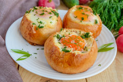 Eieren in een broodje met ham, kaas en kruiden worden gebakken dat royalty-vrije stock afbeeldingen