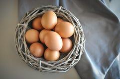 Eieren in een houten mand stock afbeeldingen