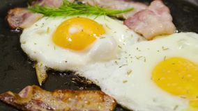 Eieren en bacon, met kruiden die in een pan braden stock videobeelden