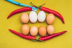 Eieren en Spaanse peper in de vorm van een mond met tanden De witte eieren zijn gebleekte tanden Gele eieren - vóór bleken stock foto