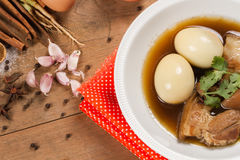 Eieren en varkensvlees in de jus worden gestoofd die stock foto