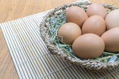 Eieren in mand op houten Stock Foto's