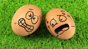 Eieren met grappige gezichten, grappige actie op groene grasrug Stock Foto