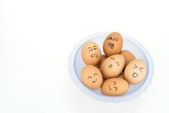Eieren met het glimlachen gelukkige gezichten op plastic die kom, op witte achtergrond worden geïsoleerd Stock Fotografie