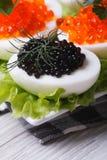 Eieren met rode en zwarte vissenkaviaar en sla Stock Foto