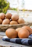Eieren op tafelkleed over houten lijst Stock Afbeeldingen