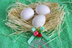 Eieren in stro op een groene handdoek Royalty-vrije Stock Afbeeldingen