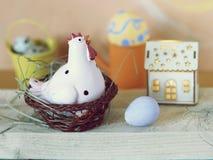 Eieren, stuk speelgoed kip, stuk speelgoed huis met verlichting, Pasen-decor royalty-vrije stock afbeeldingen