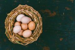 Eieren van binnenlandse kippen in rieten mand op zwarte houten retro grungeachtergrond Royalty-vrije Stock Foto