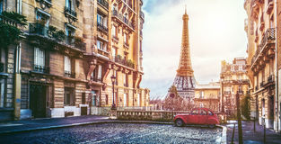 The eifel tower in Paris from a tiny street. Small paris street with view on the famous paris eifel tower on a cloudy rainy day with some sunshine Royalty Free Stock Image