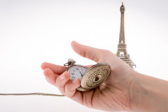 Eifel Tower and time. Hand holding a pocket watch befere Eifel Tower Royalty Free Stock Images